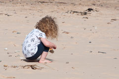 A little girl happily exploring and playing in the sand Stock Images