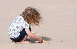 A little girl happily playing in the sand Stock Photography