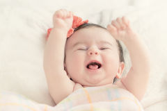 Baby who smiles. Little girl happily raises his hands up Royalty Free Stock Photos