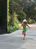 Little girl happily running along the path from the garden.  Stock Images