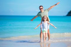 Little girl and happy dad having fun during beach vacation Stock Photos