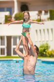 Little girl and happy dad having fun together in Stock Photography