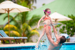Little girl and happy dad having fun together in outdoors swimming pool Stock Images
