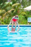 Little girl and happy dad having fun together in outdoors swimming pool Stock Photography
