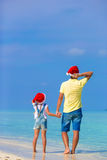 Little girl and happy dad in Santa Hat during. Little girl and happy dad in Santa Hat at exotic beach Royalty Free Stock Photos