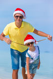 Little girl and happy dad in Santa Hat during. Little girl and happy dad in Santa Hat at exotic beach Stock Image