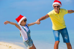Little girl and happy dad in Santa Hat during. Little girl and happy dad in Santa Hat at exotic beach Stock Images