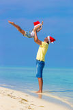 Little girl and happy dad in Santa Hat during. Little girl and happy dad in Santa Hat at exotic beach Stock Photo