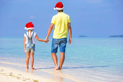 Little girl and happy dad in Santa Hat during. Little girl and happy dad in Santa Hat at exotic beach Royalty Free Stock Images