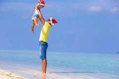 Little girl and happy dad in Santa Hat during. Little girl and happy dad in Santa Hat at exotic beach Royalty Free Stock Photography