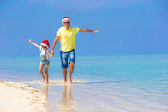 Little girl and happy dad in Santa Hat during. Little girl and happy dad in Santa Hat at exotic beach Royalty Free Stock Photo