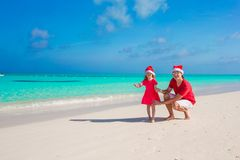 Little girl and happy dad in Santa Hat at exotic. Young father and adorable little daughter in Christmas Hat Royalty Free Stock Image