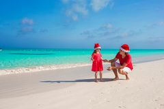 Little girl and happy dad in Santa Hat at exotic. Young father and adorable little daughter in Christmas Hat Stock Photo