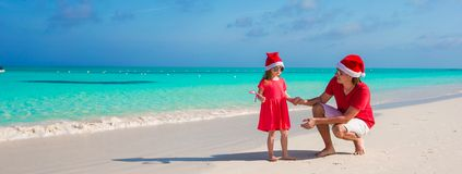 Little girl and happy dad in Santa Hat at exotic. Young father and adorable little daughter in Christmas Hat Stock Photos
