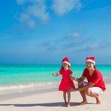 Little girl and happy dad in Santa Hat at exotic. Young father and adorable little daughter in Christmas Hat Stock Images
