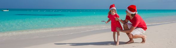 Little girl and happy dad in Santa Hat at exotic. Young father and adorable little daughter in Christmas Hat Royalty Free Stock Photos