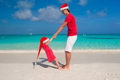 Little girl and happy dad in Santa Hat have fun at. Young father and adorable little daughter in Christmas Hat Stock Image