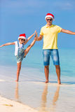 Little girl and happy dad in Santa Hats enjoy Christmas vacation. Little girl and happy dad in Santa Hat at exotic beach Stock Photo
