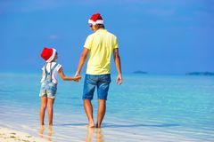 Little girl and happy dad in Santa Hats enjoy. Little girl and happy dad in Santa Hat at exotic beach Stock Images