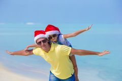 Little girl and happy dad in Santa Hats enjoy. Little girl and happy dad in Santa Hat at exotic beach Royalty Free Stock Photos