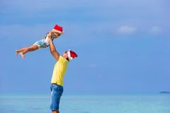 Little girl and happy dad in Santa Hats enjoy. Little girl and happy dad in Santa Hat at exotic beach Stock Image