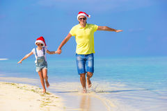 Little girl and happy dad in Santa Hats enjoy. Little girl and happy dad in Santa Hat at exotic beach Stock Photos