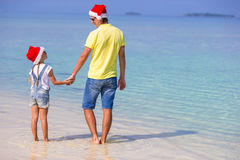 Little girl and happy dad in Santa Hats enjoy. Little girl and happy dad in Santa Hat at exotic beach Royalty Free Stock Photography