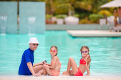 Little girl and happy father having fun on the edge of swimming pool. Little girl and happy dad having fun on the edge of swimming pool Stock Photography