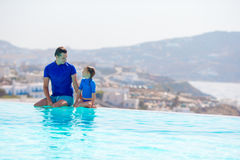 Little girl and happy father having fun on the edge of swimming pool Stock Photos