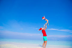 Little girl and happy father in Santa Hat during. Little girl and happy dad in Santa Hat at exotic beach Royalty Free Stock Image