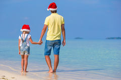 Little girl and happy father in Santa Hat during. Little girl and happy dad in Santa Hat at exotic beach Royalty Free Stock Images
