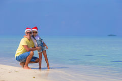 Little girl and happy father in Santa Hat during. Little girl and happy dad in Santa Hat at exotic beach Royalty Free Stock Photos