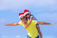 Little girl and happy father in Santa Hats enjoy. Little girl and happy dad in Santa Hat at exotic beach Stock Photo