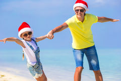 Little girl and happy father in Santa Hats enjoy. Little girl and happy dad in Santa Hat at exotic beach Royalty Free Stock Photo