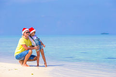 Little girl and happy father in Santa Hats enjoy. Little girl and happy dad in Santa Hat at exotic beach Stock Image