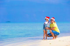 Little girl and happy father in Santa Hats enjoy. Little girl and happy dad in Santa Hat at exotic beach Stock Images
