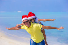 Little girl and happy father in Santa Hats enjoy. Little girl and happy dad in Santa Hat at exotic beach Royalty Free Stock Image
