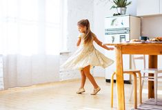 Little girl in golden dress dancing on kitchen, Christmas decorations royalty free stock photo