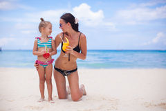 Little girl and happy mom during summer beach Stock Photos