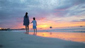 Little girl and daddy silhouette in the sunset at the beach. Little girl and happy mother silhouette in the beautiful sunset at the beach. Amazing colors of sky stock video