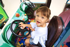 Little girl is happy sitting on the driver`s seat of the children`s car Stock Photo