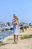 Little girl on the harbor holding a rope Stock Image
