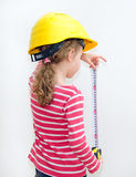 Little girl in hard hat measuring wall. Stock Photos