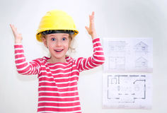 Little girl in hard hat standing near the wall. Stock Photos