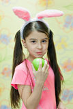 Little girl with the hare ears eats a big green apple. Little girl with paints hare ears easter eggs brush Stock Images