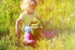 Little girl harvesting cucumbers in garden Royalty Free Stock Photos