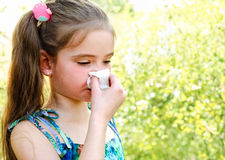 Little girl has allergy to spring blossoming and blowing her nos. E outdoor stock photo