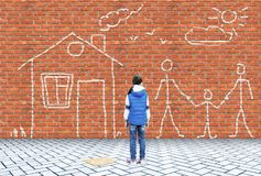 Little girl has drawn wit chalk on a wall picture with family and house. Little girl has drawn wit chalk on a brick wall picture with family and house royalty free stock image