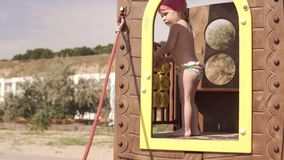 Little girl has fun at playground at sea beach in sunny day stock video