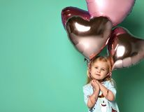 Little girl has fun with a bunch of pink air balloons in the shape of her heart. stock image